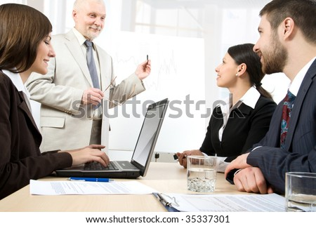 Four business people listening to a  speaker