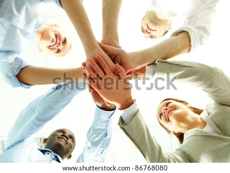 Four business people putting their hands on hands of their colleagues - stock photo