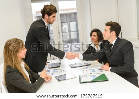 Four business people shaking hands, finishing up a meeting