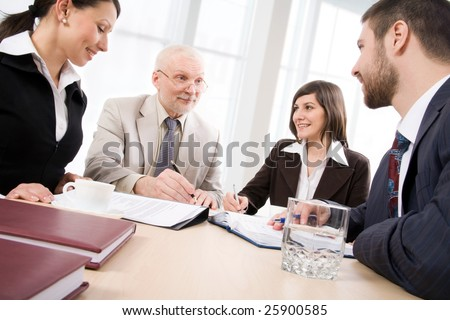 Four business people sit round a table and communicate
