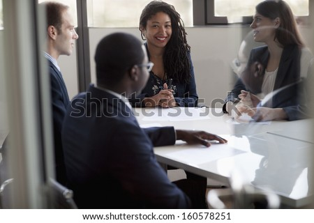 Four business people sitting and discussing at business meeting - stock photo