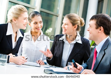 Four business people sitting at the table and discussing a project - stock photo
