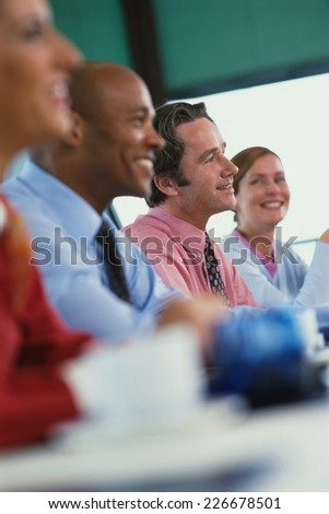 Four business people sitting in a conference room - stock photo
