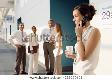 Four business people talking in corridor outside meeting room, focus on businesswoman using mobile phone, smiling - stock photo