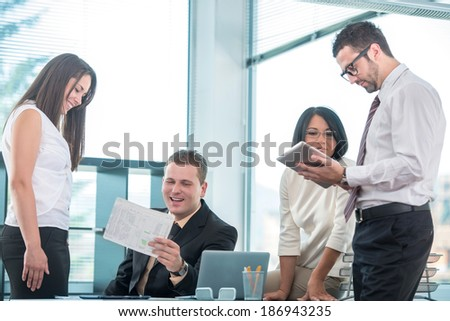 Four business people working with laptop in modern office