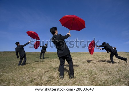 Four businessman with red umbrellas on the nature - stock photo