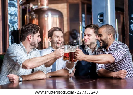 Four businessmen drink beer and rejoice together at the bar. Successful businessmen friends having fun together in the bar with a beer. - stock photo