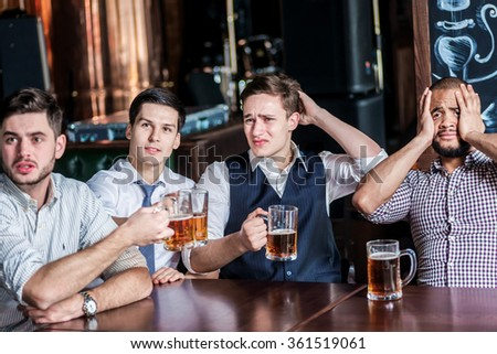 Four businessmen fans drinking beer and rejoice and shout together watching TV at the bar. Confident business people having fun with friends at the bar with a beer watching football on TV - stock photo