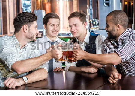 Four businessmen friends drink beer and spend time together in a bar. Confident business people having fun with friends at the bar with a beer at the table - stock photo