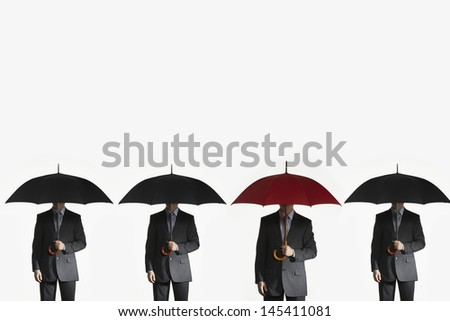 Four businessmen holding umbrellas in a line against white background - stock photo