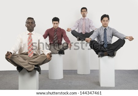 Four businessmen practicing yoga - stock photo