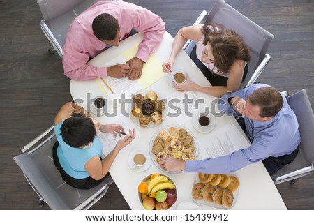 Four businesspeople at boardroom table with breakfast - stock photo