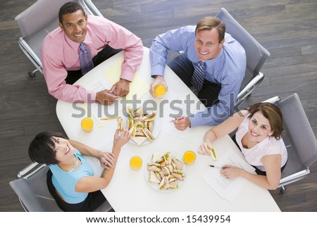 Four businesspeople at boardroom table with sandwiches smiling - stock photo