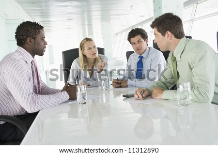 Four businesspeople having meeting around table - stock photo