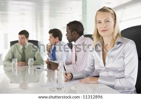 Four businesspeople having meeting in boardroom - stock photo