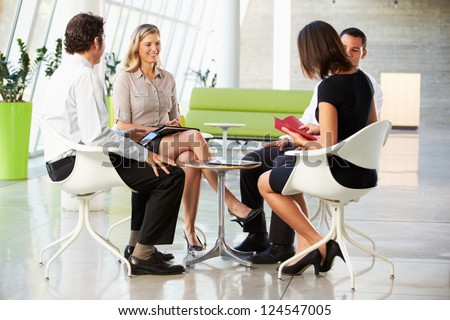 Four Businesspeople Having Meeting In Modern Office - stock photo