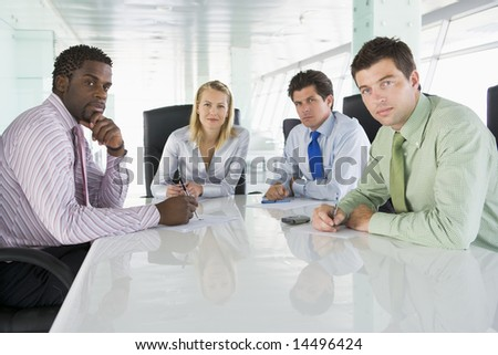 Four businesspeople in a boardroom - stock photo