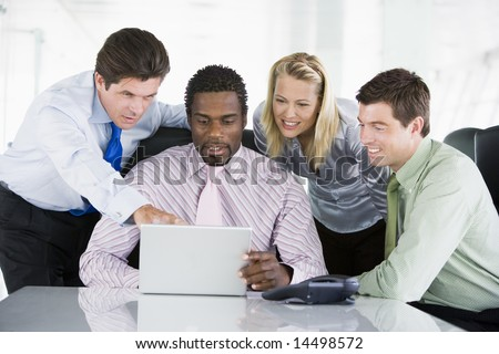 Four businesspeople in a boardroom pointing at laptop and smiling - stock photo