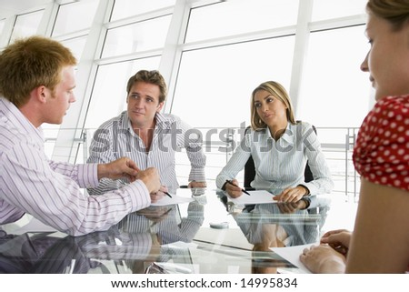 Four businesspeople in a boardroom with paperwork - stock photo