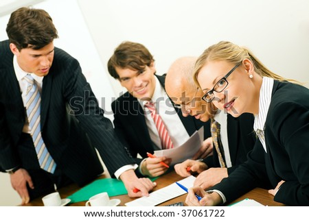 Four businesspeople in a team meeting sitting around a conference table - stock photo