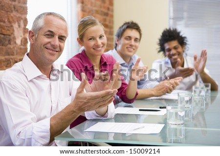 Four businesspeople in boardroom applauding and smiling - stock photo