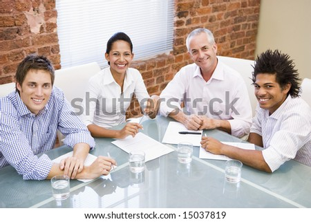 Four businesspeople in boardroom smiling - stock photo