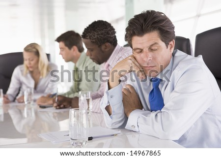 Four businesspeople in boardroom with one businessman sleeping - stock photo