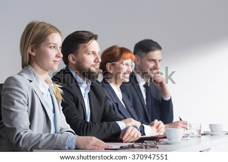Four businesspeople in elegant style sitting beside table