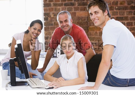 Four businesspeople in office space smiling