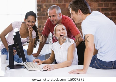 Four businesspeople in office space with computer smiling - stock photo
