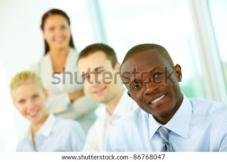 Four businesspeople looking at camera and smiling, the focus is on African American