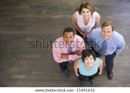 Four businesspeople standing indoors smiling - stock photo