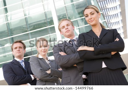 Four businesspeople standing outdoors smiling - stock photo