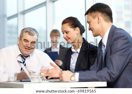 Four businesspeople working together in office - stock photo