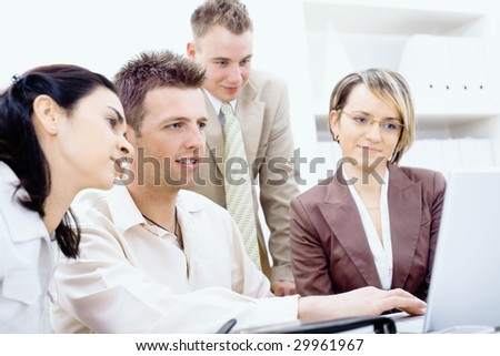 Four businesspeople working together in office, using laptop computer, smiling.