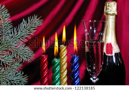 Four candle and   goblet of champagne  against purple drapery - stock photo