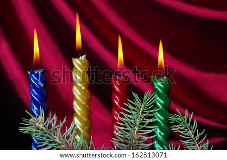 Four candle, goblet of champagne and new year decoration against purple drapery - stock photo