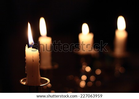 Four candles in the darkness - stock photo