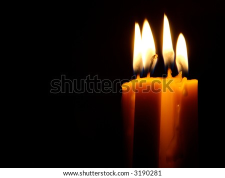 Four Candles isolated over dark background.