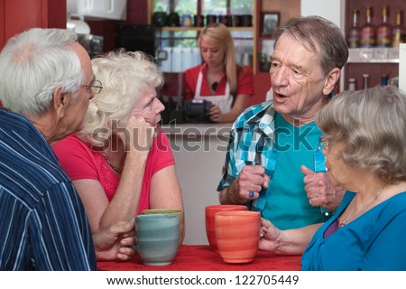 Four Caucasian senior adults with coffee mugs in conversation - stock photo