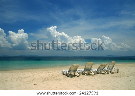 Four chair facing beautiful cloud at the beach - stock photo