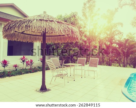 Four chairs and table standing beside the public pool in vintage style. - stock photo