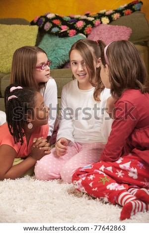 Four chatty little girls in pajamas at a sleepover - stock photo