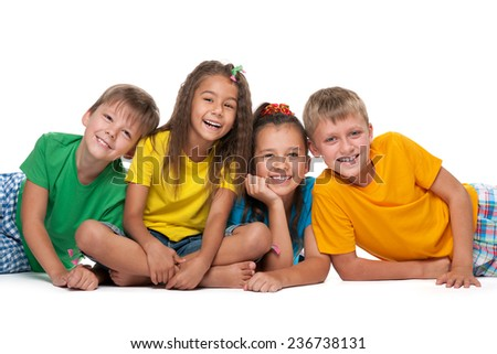 Four cheerful children are lying on the white background - stock photo