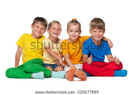 Four cheerful children sit on the white background - stock photo