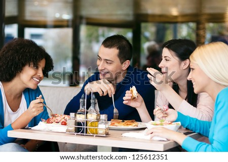 Four cheerful friends chatting while lunch in restaurant