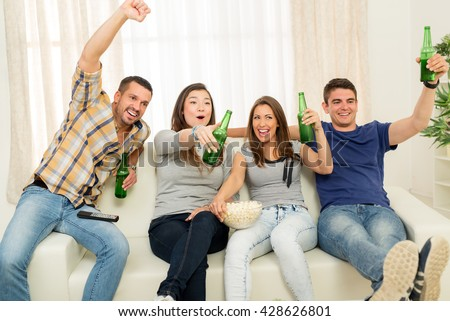 Four cheerful friends hanging out in an apartment and watching a football game together. They cheering, drinking beer and eating popcorn.