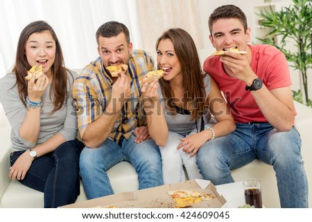 Four cheerful friends hanging out in an apartment. They eating pizza and looking at camera.
