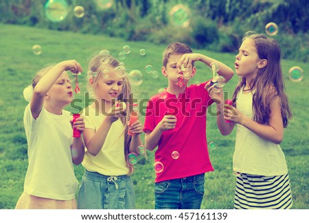 Four cheerful kids in school age sitting together in park and blowing soap bubbles - stock photo