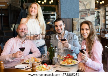Four cheerful people sitting at restaurant table - stock photo